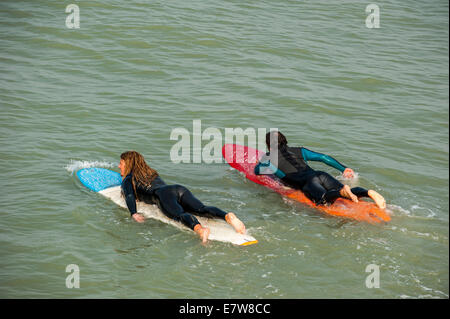 Surfer lying flat on his surfboard, paddling out towards ...