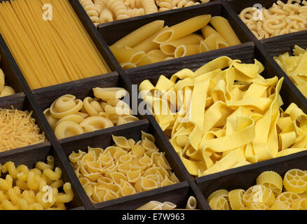 lots of various noodles in a wooden box - Stock Photo