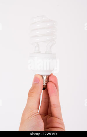 Affordable light bulb holding by male human hand on white. - Stock Photo