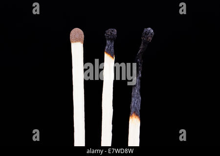 One healthy and two burnt matches in row, isolated on dark background. - Stock Photo