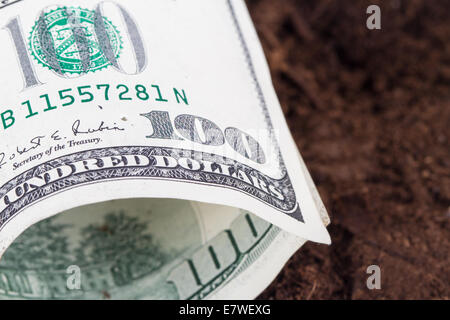 One hundred dollar banknote on soil for growing. - Stock Photo