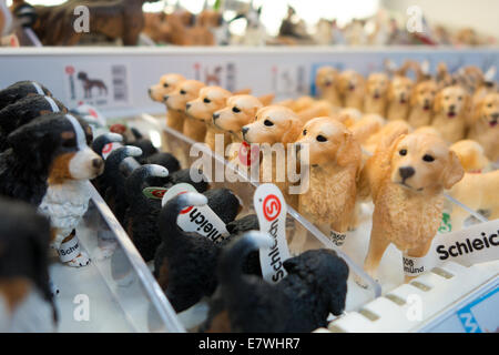 Rows of toy dog figurines are lined up on a shelf in a toy store. Golden retrievers and other breeds. - Stock Photo