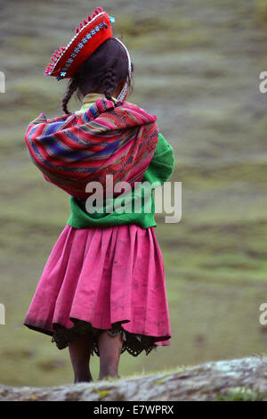 Girl wearing traditional costume, rear view, Andes, near Cusco, Peru - Stock Photo