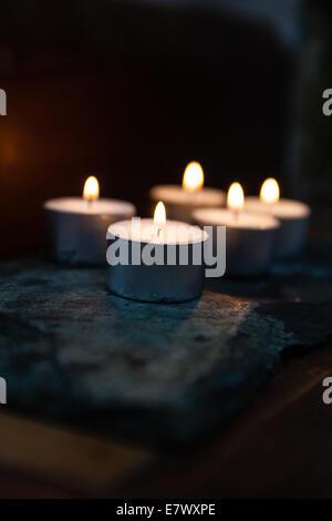 Candles emit a warm glow on a Buddhist shrine - Stock Photo