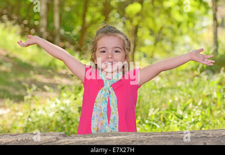 little girl enjoying and raising her hands in park - Stock Photo