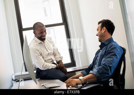 Office life. A man leaning back in an office chair talking to a colleague sitting on the edge of the desk. - Stock Photo