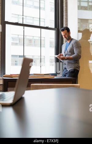 Office life. A man standing by a window in an office checking his smart phone. - Stock Photo