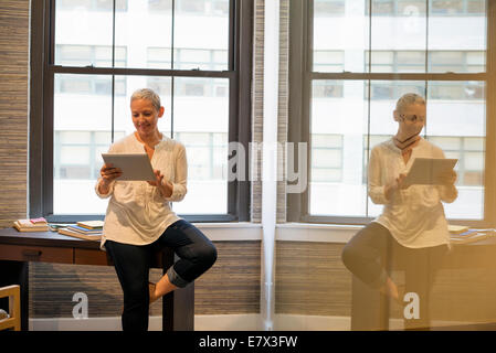 Office life.A woman seated on the edge of her desk using a digital tablet. - Stock Photo