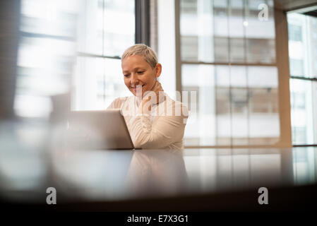 Office life. A woman seated using a laptop computer. - Stock Photo