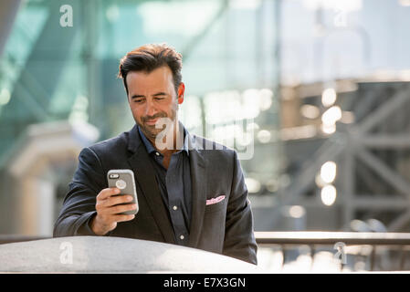 A man seated on a bench checking his smart phone. - Stock Photo