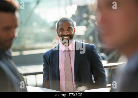A business man seated smiling confidently, in a group with two others. - Stock Photo