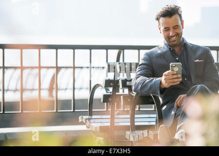 A businessman seated checking his phone, laughing. - Stock Photo