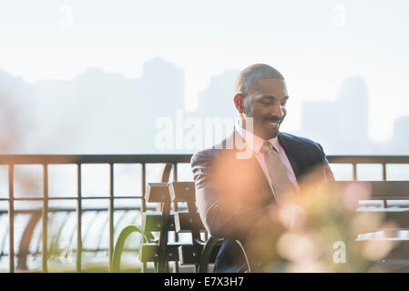 A businessman seated checking his phone, smiling. - Stock Photo