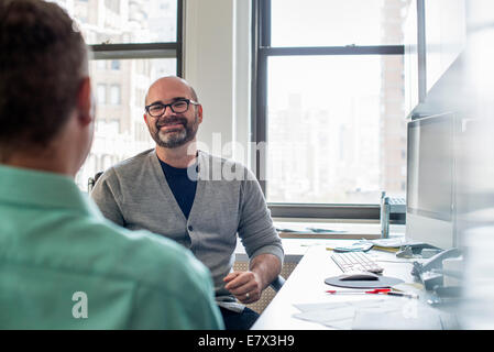 Two men seated in a light airy office environment, talking. - Stock Photo