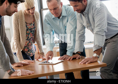 Four people, three man and a woman leaning over a digital tablet on a table. - Stock Photo