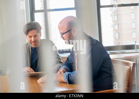 Two business colleagues in an office talking and referring to a digital tablet. - Stock Photo