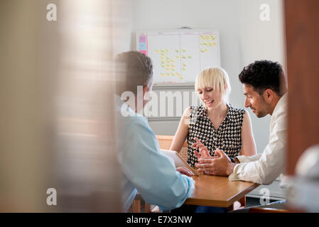 Three business colleagues in an office talking around a table and looking at a digital tablet. - Stock Photo
