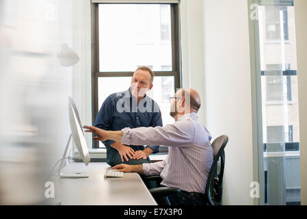 Two business colleagues in an office talking and referring to a computer screen.