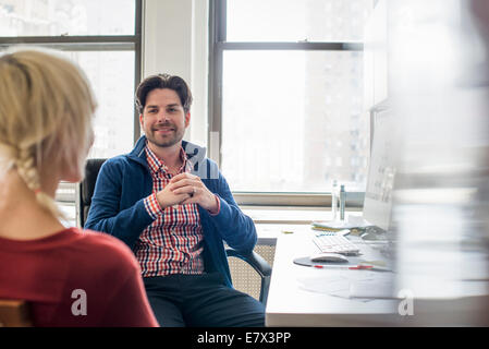 Office life. A man and woman in an office, seated talking to each other. - Stock Photo
