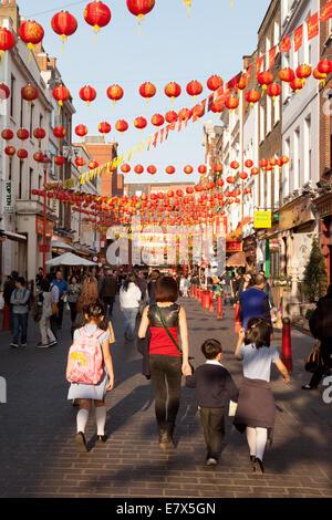 A chinese family walking in Gerrard Street, Chinatown, London Soho UK - Stock Photo
