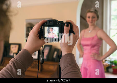 A mother taking a picture of her daughter in a prom dress. - Stock Photo