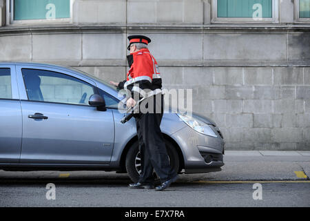 A traffic warden (civil enforcement officer) on patrol issuing parking tickets to illegally parked cars in Cardiff, - Stock Photo