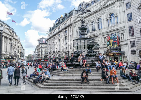 Piccadilly Circus,London, Tourists sit on the Steps of the Eros Statue - Stock Photo