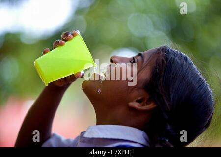 Indian school girl drinking water from a plastic glass - Stock Photo