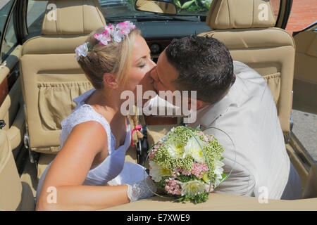 Bride and groom kissing in the back seat of an open car, convertible - Stock Photo