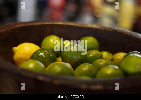 Big bowl of lemons and limes in a restaurant. - Stock Photo