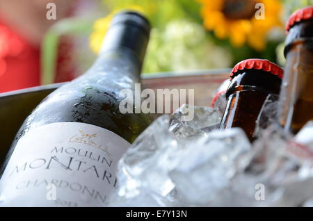 Wine and beer bottles in an ice bucket - Stock Photo