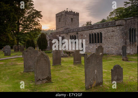 Exterior of St Michael and All Angels Church with headstones in churchyard under colourful sky at sunset - Hubberholme, - Stock Photo