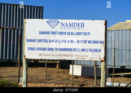 NAMDEB diamond mining company warning sign against diamond theft and containers in the background, Lüderitz, Namibia - Stock Photo