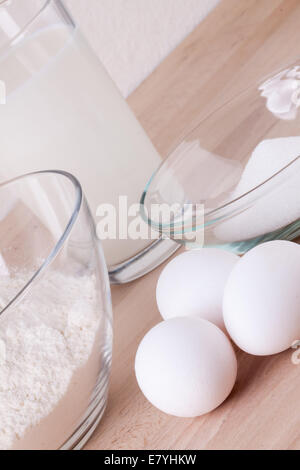 Baking ingredients in the kitchen with a bowl of flour, eggs, sugar, jug of milk and butter ready to bake a cake - Stock Photo