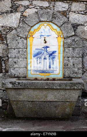 Ceramic and stone drinking fountain next to street, Vila Praia de Ancora , northern Portugal - Stock Photo
