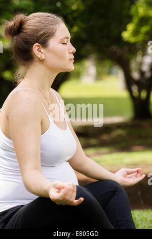 Portrait of white beautiful pregnant woman doing yoga exercise in park sitting on grass, lotus position - Stock Photo