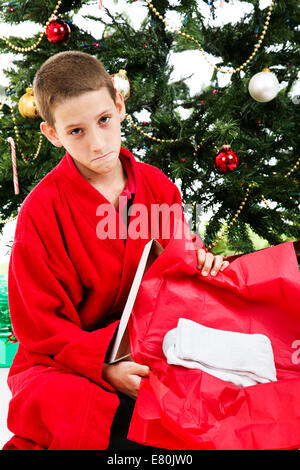 Little boy opening a wrapped present of socks on Christmas morning. - Stock Photo