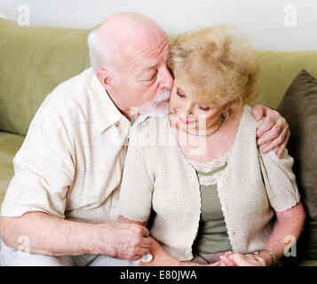 Elderly husband kissing his wife on the cheek in a gesture of consolation and love. - Stock Photo