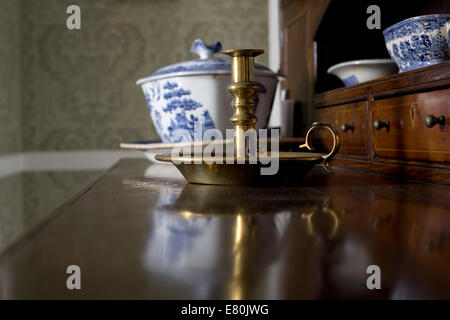 Charles Dickens birthplace museum with brass candlestick holder and painted china on polished wood of a dresser - Stock Photo