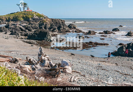 California, Crescent City, Battery Point Lighthouse built 1856, couple with two dogs playing on beach - Stock Photo