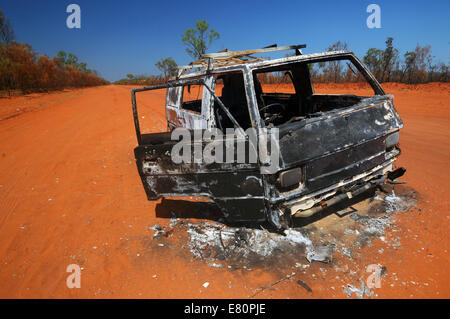 Burnt-out wreck of vehicle in middle of road to Cape Leveque, Dampier Peninsula, Kimberley region, Western Australia. - Stock Photo