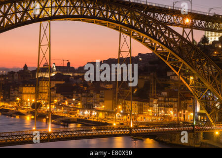 Early evening sunset over Oporto and the Douro river with the illuminated Luiz I bridge in foreground, Portugal - Stock Photo