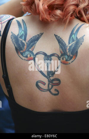 A woman with a double swallow design on her shoulder blades at the 10th International London Tattoo Convention, - Stock Photo
