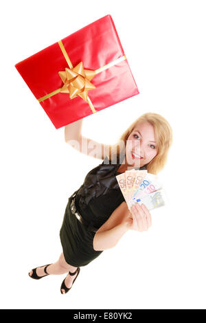 Happy smiling blonde girl young woman holding red christmas gift box and euro currency money banknotes. Holidays - Stock Photo
