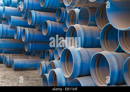 Large diameter plastic pipes lay stacked, ready for use, in the storage yard of a large open cast copper mine. - Stock Photo