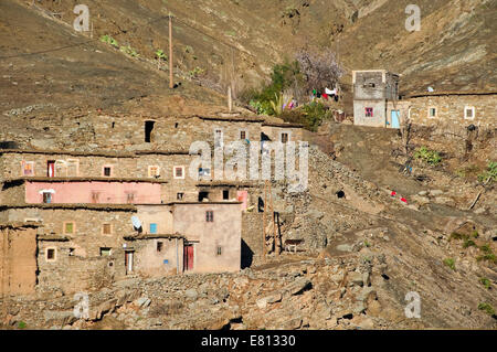 Horizontal view of a small mudbrick village nestled in the High Atlas Mountain range in Morocco. - Stock Photo