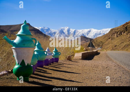 Horizontal close up of a row of giant teapots on the roadside in the High Atlas Mountain range in Morocco. - Stock Photo