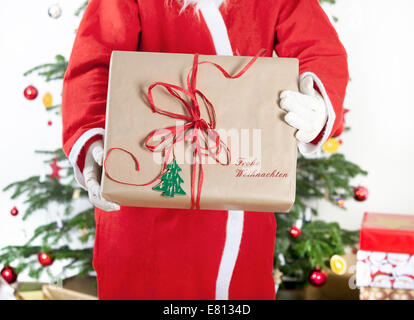 Santa Claus brings gifts in the background, a Christmas tree - Stock Photo