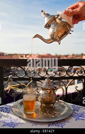Vertical close up of traditional mint tea poured from a height into small glasses overlooking Place Jemaa el-Fnaa - Stock Photo