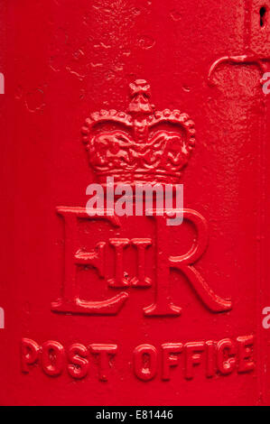Vertical close up of the embosed ER II initials on the front of a bright red postbox. - Stock Photo